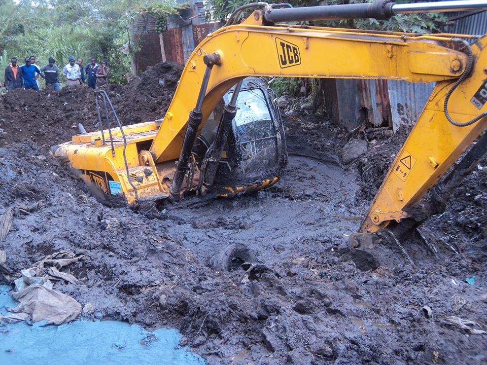 Image of excavator immersed in mud digging it's way out.