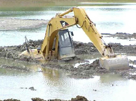 Excavator immersed in mud digging it's way out.
